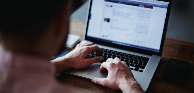 man typing laptop feat