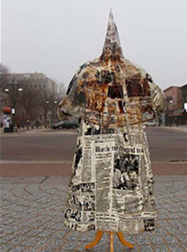 A professor was required to remove his artwork — a Ku Klux Klan robe covered in newspaper images of racial violence — from an open area of campus.
