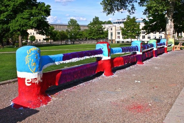 A fence on Carnegie Mellon University's campus, clearly colorfully painted over multiple times.