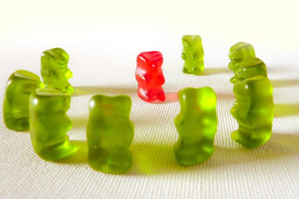 A group of green gummy bears surrounding a red gummy bear in a threatening manner.