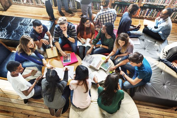 College students studying around a table in a common area.