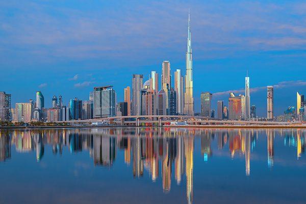View on Dubai skyline with reflection in the river at sunrise, Dubai, United Arab Emirates