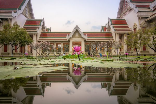 Traditional Thai style building reflects on the pool surface with pink lotus in the centre, Chulalongkorn university Bangkok, Thailand.